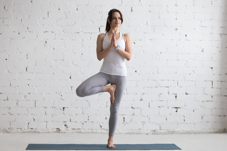 stress relief: Beautiful smiling happy young woman working out indoors, doing yoga exercise on blue mat, standing in Vrksasana Posture, Tree Pose, full length