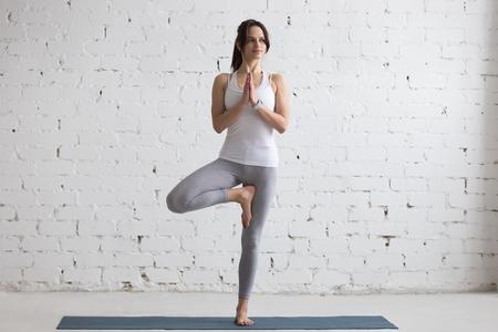 jovenes felices: Hermosa sonriente mujer joven feliz trabajando en el interior, haciendo ejercicios de yoga en la estera azul, de pie en vrksasana postura, actitud del árbol, de cuerpo entero Foto de archivo