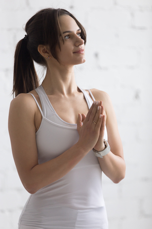 namaste: Indoors portrait of beautiful happy young woman with arms folded in Namaste gesture