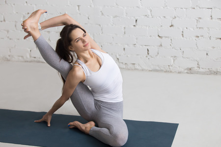parivrtta: Beautiful happy young woman working out indoors, doing yoga exercise on blue mat, sitting in Parivrtta Surya Yantrasana, Compass or Sundial Posture, full length, copy space