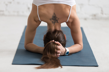 human arm: Beautiful young woman with flower tattoo on her back working out indoors, doing yoga exercise on blue mat, supported headstand posture, salamba sirsasana, rear view, close-up