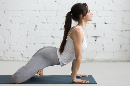 knee bend: Beautiful happy young woman working out in loft interior, doing hip opener exercise, yoga workout on blue mat, full length