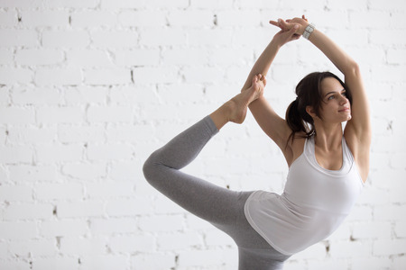 Portrait of attractive happy young woman working out indoors, doing yoga exercise, variation of Natarajasana, Lord of the Dance, King Dancer or Standing Mermaid Pose, copy space