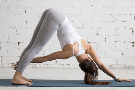 revolved: Beautiful young woman working out indoors, doing yoga exercise in the room with white walls, Revolved Downward-Facing Dog Pose, Parivrtta Adho Mukha Svanasana, full length, back view Stock Photo