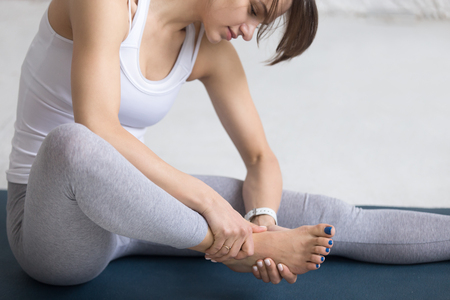 relieving pain: Beautiful young woman massaging her foot during sport work out indoors, close-up