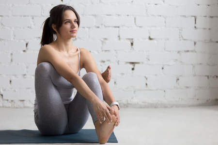 women hips: Beautiful young woman working out in loft interior, doing Seated Hip Stretch, hip opener Eka Pada Agni Stambhasana, warming up on blue mat during practice, full length, copy space