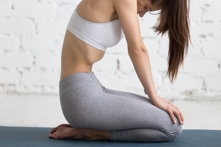 lock out: Beautiful young woman working out in loft interior, doing yoga exercise on blue mat, holding the breath while performing Upward Abdominal Lock, Uddiyana Bandha, close-up