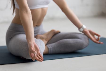 persona respirando: mujer joven hermosa que se resuelve en el interior de loft, haciendo ejercicios de yoga en la estera azul, sentado en Ardha Padmasana, Medio Loto Postura, la meditaci�n, la respiraci�n, primer plano