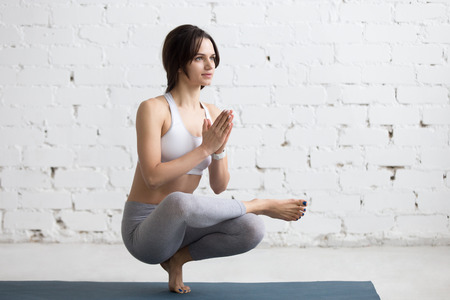 anjali: Attractive calm young woman working out in loft interior, doing yoga exercise, sitting in squat with hands in Anjali Mudra, doing Toestand pose, variation of Utkatasana, full length