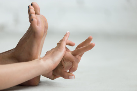 gyan: Beautiful young woman working out indoors, doing yoga exercise, stretching, holding hands in Gyan Mudra - Mudra of Knowledge, close-up, copy space Stock Photo