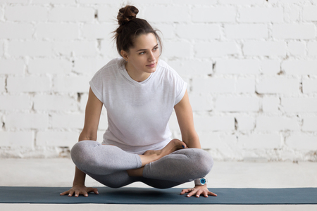 Beautiful young woman working out in loft interior, doing yoga exercise on blue mat, arm balance exercise with crossed legs, Scale Posture, Tolasana, Utpluthi Pose, full length 版權商用圖片 - 53155657