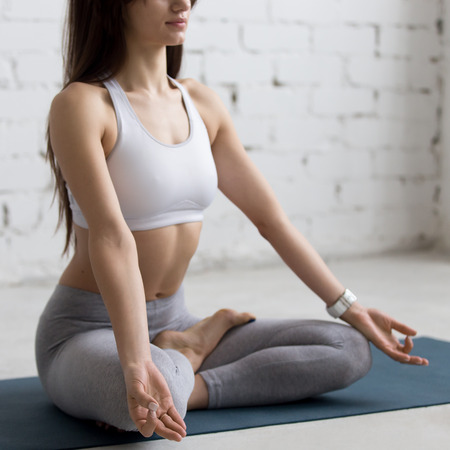 Attractive young woman working out in loft interior, doing yoga exercise on blue mat, Sitting in Ardha Padmasana, Half Lotus Posture, meditating, breathing, closeup Stock Photo