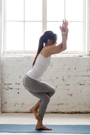 beautiful ankles: Beautiful young woman working out on blue mat in loft interior, doing yoga exercise for ankles, calves, thighs, hips and shoulders, Eagle Pose, Garudasana, full length