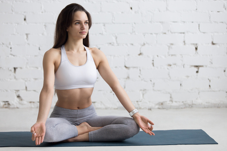 mudra: Beautiful young woman working out in loft interior, doing yoga exercise on blue mat, Sitting in Easy (Decent, Pleasant Posture), Sukhasana, asana for meditation, pranayama, full length, copy space Stock Photo