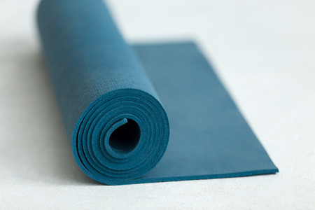 Rolled up blue yoga, pilates or exercise mat on the floor, close up