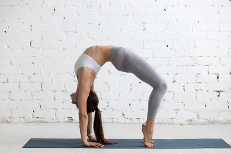 dhanurasana: Beautiful young woman working out in loft interior, doing yoga exercise on blue mat, stretching, standing in Bridge Pose, Urdhva Dhanurasana (Upward Bow), Chakrasana (Wheel) Posture, full length