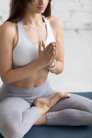 Attractive young woman working out in loft interior, doing yoga exercise on blue mat, Sitting in Ardha Padmasana with palms in Namaste, Half Lotus Posture, meditating, breathing, closeup