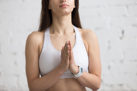 Attractive young woman working out in loft interior, doing yoga exercise with palms in Namaste, meditating, breathing, closeup Stock Photo