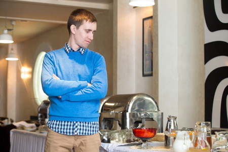 fedup: Portrait of young man at self-catering breakfast in hotel restaurant, picky eater fed-up with food, showing disappointment on his face Stock Photo