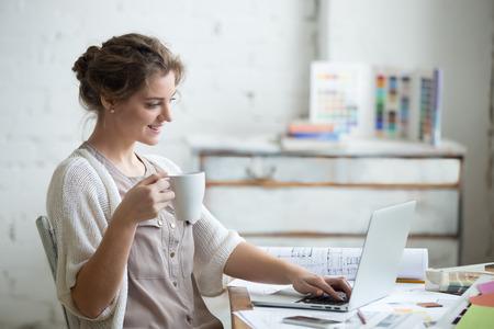 Retrato de hermosa feliz sonriente mujer joven diseñador sentado en su casa escritorio de oficina con la taza de café, que trabaja en la computadora portátil en el desván entre otras. Modelo atractivo alegre usando la computadora, escribiendo. Adentro Foto de archivo