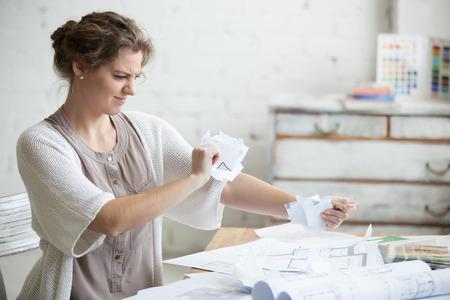 Ritratto di giovane sottolineato donna seduta al tavolo in un piccolo ufficio o casa indossa abbigliamento casual intelligente arrabbiato con il lavoro, che strappa i documenti con espressione facciale frustrato. emozioni umane negative