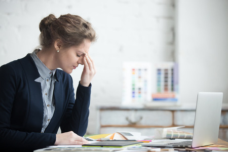 Portrait of young stressed woman sitting at home office desk in front of laptop, touching head with tired facial expression, having headache, low or high arterial blood pressure, stress