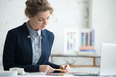 interior shot: Portrait of beautiful young designer woman working at office desk. Attractive model looking at color samples for design project. Interior shot