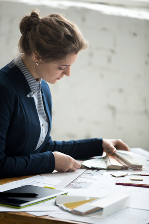 interior shot: Portrait of beautiful young designer woman wearing suit working at new project with drafts and color swatches at office desk. Attractive model choosing material samples. Interior shot Stock Photo
