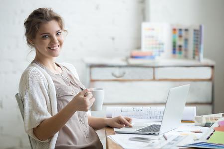 mujeres trabajando: Retrato de hermosa feliz sonriente mujer joven diseñador sentado en su casa escritorio de oficina con la taza de café, posando, mirando a la cámara. Modelo atractivo alegre usando la computadora. Adentro