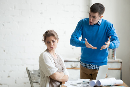 scolded: Portrait of two coworkers arguing at work. Staff in the middle of argument at modern office. Young furious man yelling at annoyed stressed woman with crossed arms. Negative human emotions Stock Photo