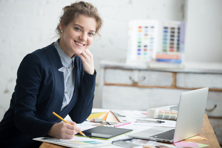 interior shot: Portrait of beautiful cheerful young designer woman working at home office desk. Attractive model wearing suit holding pencil and looking at camera with friendly expression. Interior shot Stock Photo