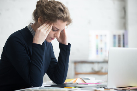 Portrait of young stressed woman sitting at home office desk in front of laptop, touching head with frustrated facial expression, having headache, overworked or depressed
