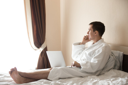 bath robe: Portrait of attractive smiling young barefoot man wearing white bath robe sitting on bed with laptop, male model talking on cellphone, using smartphone, making a call with happy expression