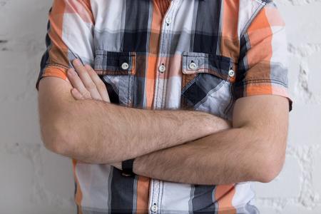 comunicacion no verbal: Casual hombre joven de pie con los brazos cruzados sobre el pecho, no verbal concepto de comunicación, primer plano Foto de archivo