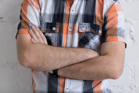 nonverbal communication: Casual young man standing with arms crossed on his chest, nonverbal communication concept, close-up Stock Photo