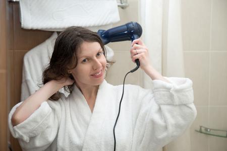 Portrait de jeune femme heureuse souriante portant un peignoir blanc en utilisant un sèche-cheveux dans la salle de bain, se préparer, sécher les cheveux après la douche en face de miroir, vue de face Banque d'images - 53245745