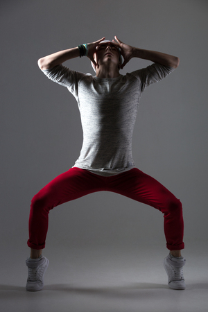 on tiptoes: Portrait of one attractive fit young man dancing, working out wearing casual clothing. Modern style cool dancer standing on tiptoes in shadow. Full length photo image on studio gray background Stock Photo