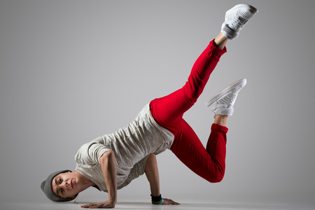 One fit handsome modern style dancer young man in casual red pants and beanie working out, performing breakdance moves, hand stand on the floor. Full length photo, studio gray background