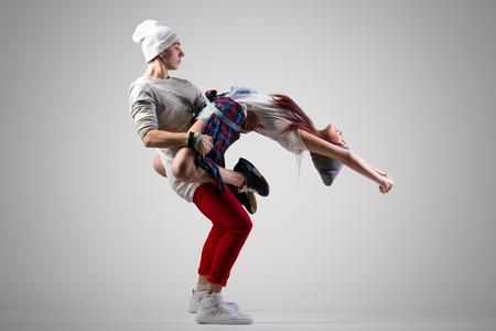 Leidenschaftliche attraktiv beiläufig tanzendes Paar. Zwei moderne Stil schöne Tänzer trainieren. Junger Mann mit seinem Mädchen Partner halten. In voller Länge Bild, Studio grauen Hintergrund