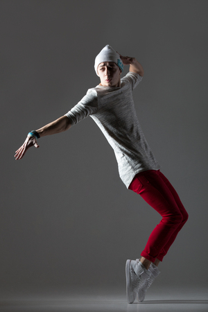 on tiptoes: Portrait of one attractive fit young man dancing, working out wearing casual red pants and beanie. Modern style cool dancer guy training, balancing on tiptoes. Full length photo image on studio gray background Stock Photo