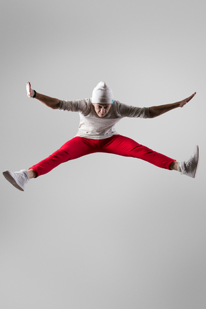 breakdancer: One young urban style breakdancer guy in casual red pants and beanie working out, dancing and jumping. Full length photo on studio gray background