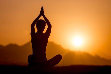 sukhasana: Silhouette of young woman sitting in yogic sukhasana easy posture in picturesque mountainous landscape, watching sunset or sunrise, meditating