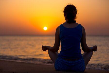 sukhasana: Serene young woman doing yoga training on the beach, Sitting in Easy (Pleasant Pose), Sukhasana, meditating, relaxing at sunset or sunrise, back view