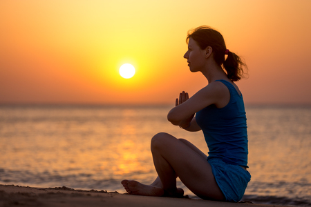 namaste: Profile of serene young woman relaxing on the beach sitting with crossed legs in yoga Easy Pose, Sukhasana, meditating with hands in Namaste gesture, at sunset or sunrise