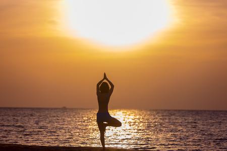 vriksasana: Young woman doing sport practice at seashore in warm summer sunlight, standing in asana vriksasana (Tree Pose), hands above the head, back view