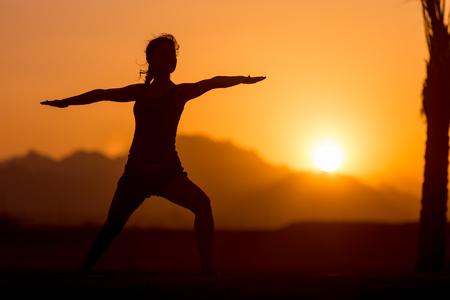 Silhouette di una giovane donna praticare lo yoga o pilates al tramonto o alba in posizione incantevole in montagna, fa esercitazione di affondo, in piedi in Warrior II posa, Virabhadrasana 2