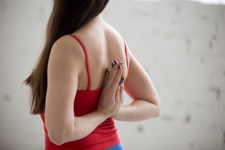 anjali: Beautiful young woman in bright colorful sportswear working out indoors in loft interior. Girl holding Anjali Mudra behind the back, exercise for flexible wrists, arms, shoulders. Close-up. Rear view Stock Photo