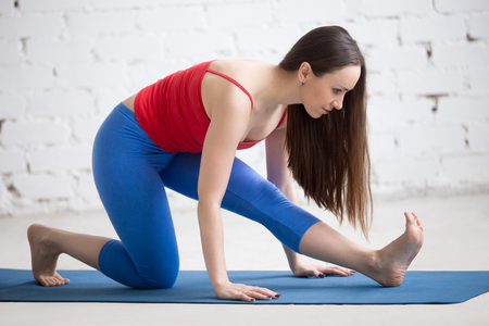 Portrait of beautiful happy young woman in colorful sportswear working out indoors. Girl doing warming up stretching exercise on blue mat, Ardha Hanumanasana (Half Monkey God Posture). Full length