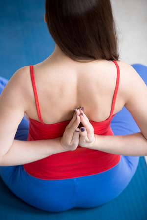 Beautiful young woman in bright colorful sportswear working out indoors on blue mat. Girl sitting in easy posture and holding Anjali Mudra behind the back. Close-up. Rear view