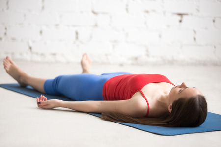 body posture: Beautiful happy young woman in bright sportswear working out indoors in loft interior on blue mat. Girl lying in Shavasana (Corpse or Dead Body Posture), resting after practice, meditating, breathing